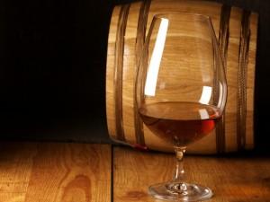 Una copa de coñac al lado de un barril de madera