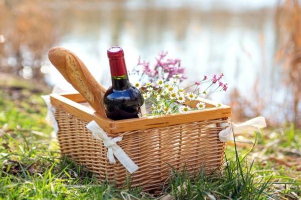 Canasta con pan, vino tinto y flores