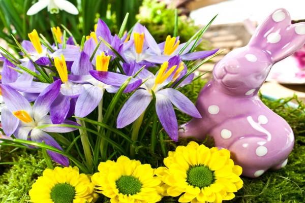 Figurita de un conejo junto a flores lilas y amarillas