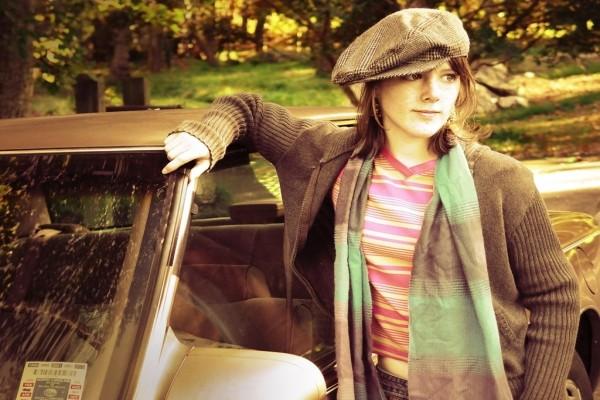 Chica joven posando junto a un coche