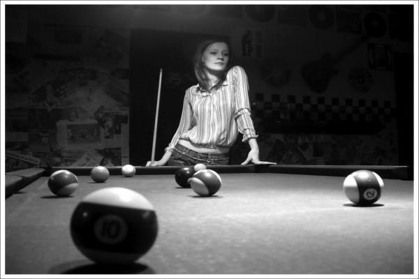 Chica jugando al billar americano