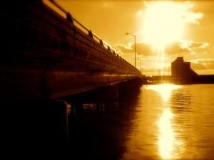 Postal: Puente iluminado por un sol dorado