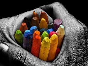 Manos sosteniendo un puñado de ceras de colores