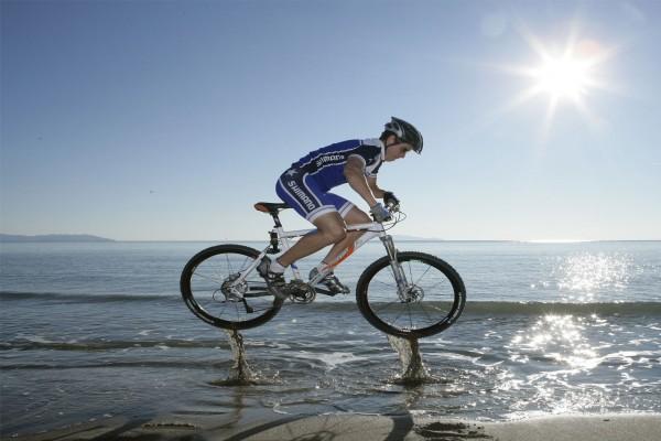Salto de una bici de montaña en la playa