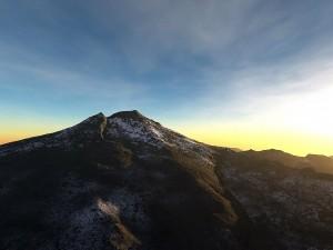 Cielo azul y dorado tras la montaña