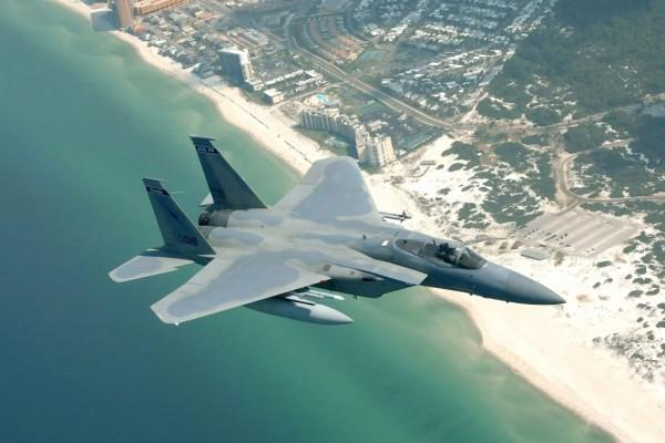 Avión de combate sobrevolando una playa