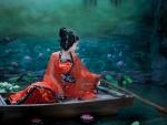 Mujer oriental navegando entre flores de loto