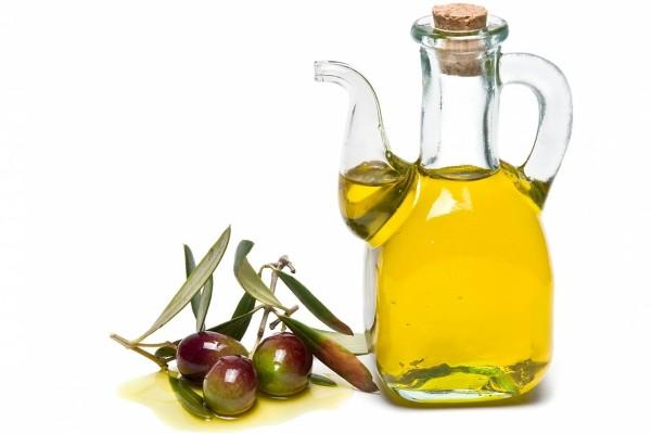 """Aceitera con """"aceite de oliva virgen extra"""" y algunas olivas"""