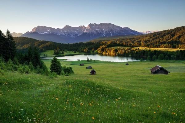 Cabañas en unas praderas al pie de los Alpes