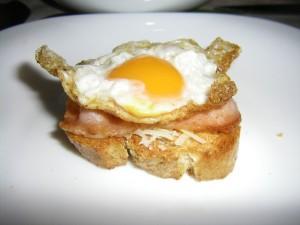 Rebanada de pan con carne y un huevo de codorniz