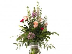 Florero de cristal con varios tipos de flores