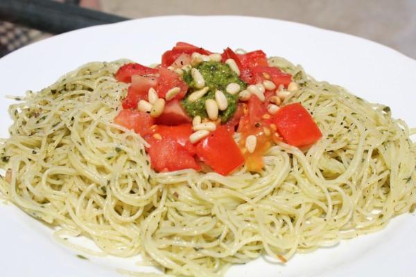 Espagueti con salsa pesto, piñones y dados de tomate natural