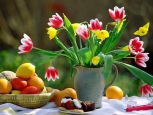 Postal: Mesa con tulipanes, frutas y un trozo de pastel