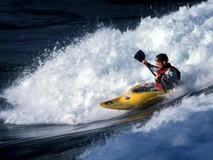 Postal: Cogiendo una ola en kayak