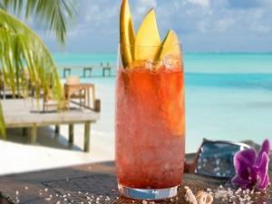 Un cóctel con mango servido en la playa
