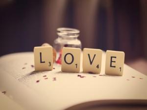 Postal: Fichas con letras formando la palabra LOVE (amor)