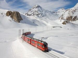 Tren atravesando un paisaje de montañas nevadas