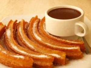Churros con azúcar y una taza de chocolate