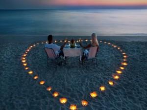 Pareja de enamorados cenando en la playa