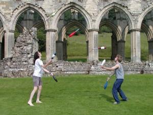 Dos malabaristas lanzando 7 mazas