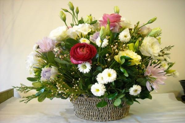 Cesta con flores variadas en tonos blancos y rosas