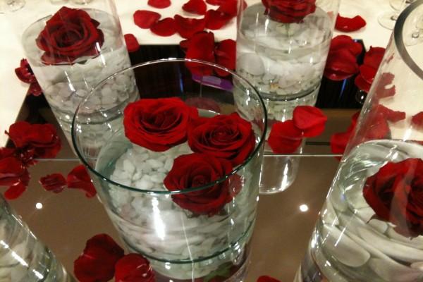 Jarrones de cristal con agua y rosas rojas