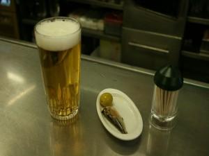Una caña (vaso de cerveza) y su tapa (sardina con oliva)