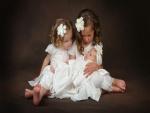 Dos nenas sosteniendo un bebé