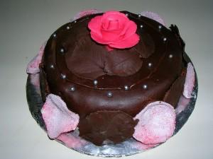 Postal: Una torta de chocolate decorada con pétalos y hojas de chocolate