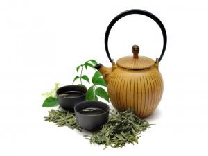 Cuencos, tetera y hojas de té verde