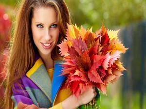 Hermosa mujer con un ramo de hojas