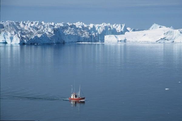 Barco navegando cerca de un fiordo de hielo en Groenlandia