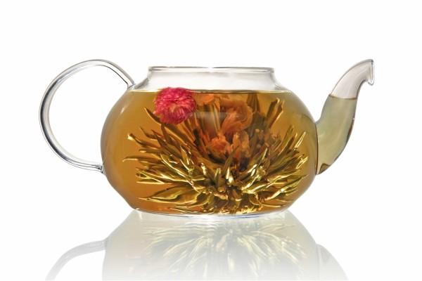 Tetera con hojas de té y flores