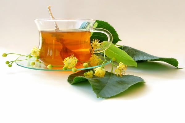Taza de té con flores y hojas verdes