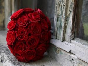 Bola de rosas rojas junto a una ventana de madera