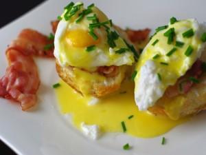 Desayuno de huevos poché con salsa holandesa y bacon