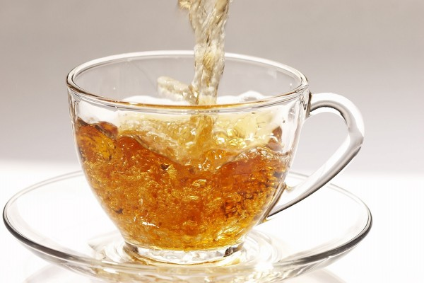 Chorro de té cayendo en la taza