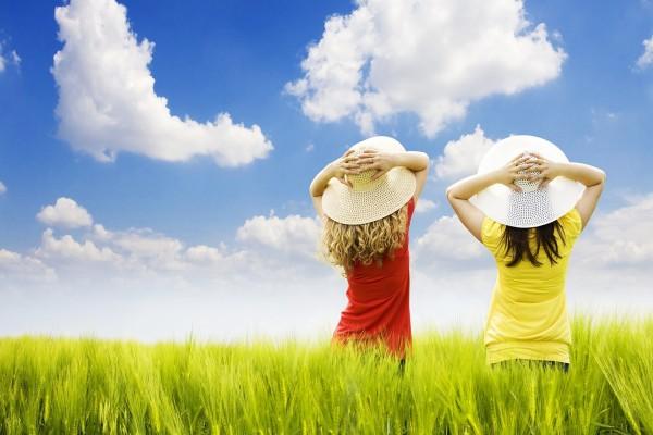Dos niñas con sombrero en un campo de verdes espigas