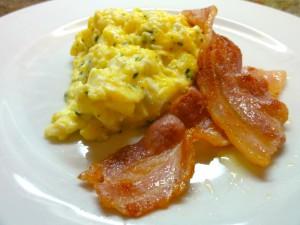 Huevos revueltos con hierbas, queso y lonchas de bacon