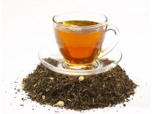 Postal: Taza de té sobre un montoncito de hojas de té