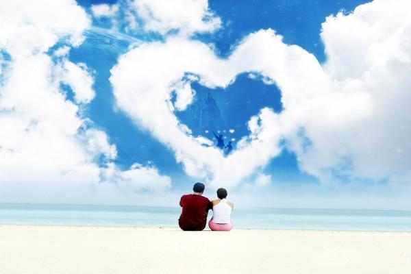 Pareja en una playa contemplando una nube con forma de corazón