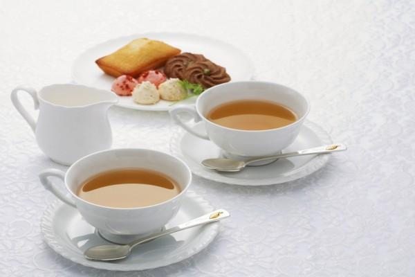 Dos tazas blancas de té con unos petits fours