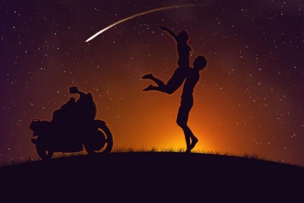 Pareja con su moto en una noche estrellada