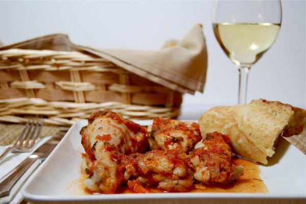 Plato de pollo con una copa de vino blanco