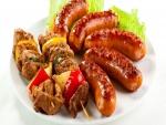 Salchichas y brochetas de carne con cebolla y tomate