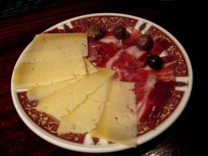 Tapa de jamón y queso con unas olivas