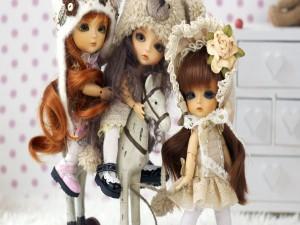 Tres muñecas junto a un caballito