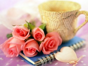 Rosas, un cuaderno y una taza
