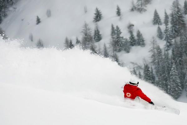 Levantando la nieve con la tabla de snowboard