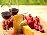Tabla de quesos, vino, granada y uvas
